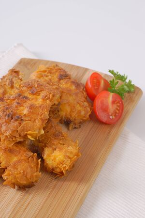 tenders: fried corn flake crusted chicken meat on wooden cutting board