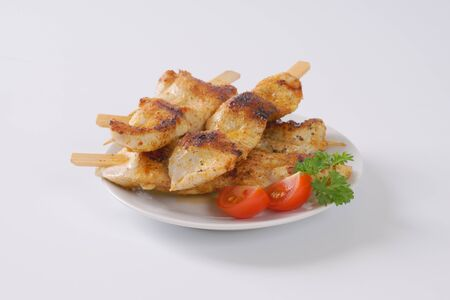 Chicken satay - grilled chicken skewers on white plate
