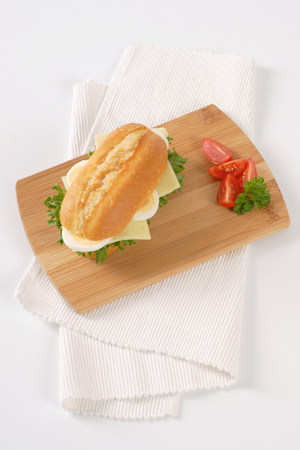 crusty roll sandwich with eggs and cheese on wooden cutting board Stock Photo