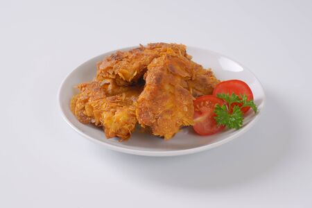 tenders: fried corn flake crusted chicken meat on white plate