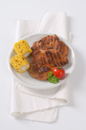 grilled pork meat steaks and corn on the cob on white plate Stock Photo
