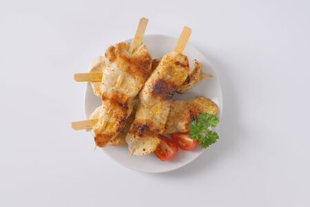 chicken satay: Chicken satay - grilled chicken skewers on white plate