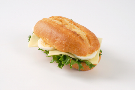 crusty roll sandwich with eggs and cheese on white background