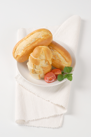 whole and sliced mini baguettes on white plate Stock Photo