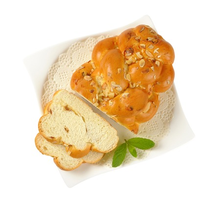 sliced loaf of sweet braided bread with almonds and raisins on white plate