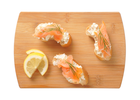 Bread based smoked salmon canapes on wooden cutting board