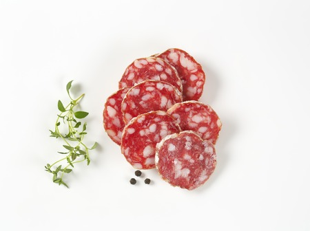 thin slices of dry cured sausage, thyme and peppercorns on white background