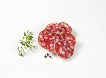 charcutería: thin slices of dry cured sausage, thyme and peppercorns on white background