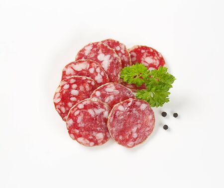charcutería: thin slices of dry cured sausage on white background