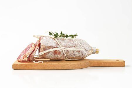 charcutería: salchicha curada seca en rodajas en tabla de cortar de madera