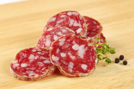 thin slices of dry cured sausage on wooden background