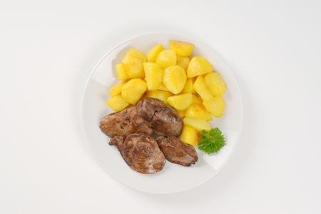 higado de pollo: plate of pan fried potatoes and chicken liver on white background