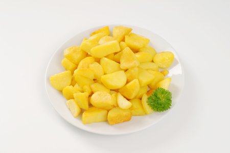 plate of pan fried potatoes on white background