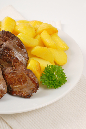 higado de pollo: plate of pan fried potatoes and chicken liver on white place mat Foto de archivo