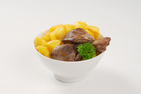 higado de pollo: bowl of pan fried potatoes and chicken liver on white background