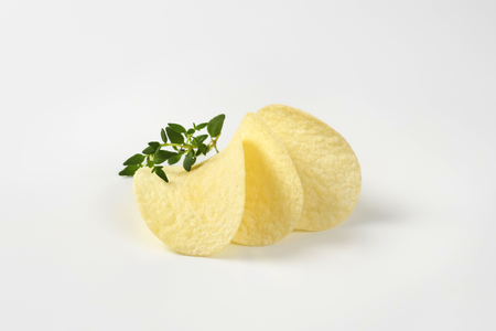 potato chips and thyme on white background