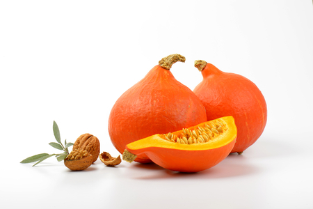 orange pumpkins with walnuts and sprig of sage on white background Stock Photo
