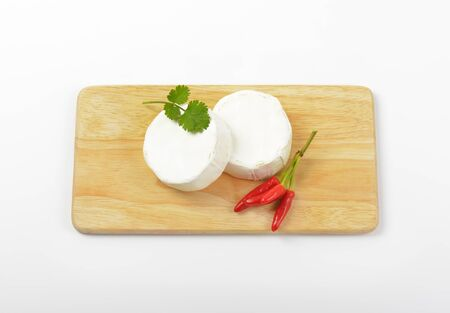 hermelin: Wheels of soft white cheese and red chili peppers on cutting board
