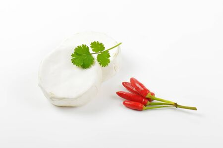 Wheels of soft white cheese and red chili peppers Stock Photo