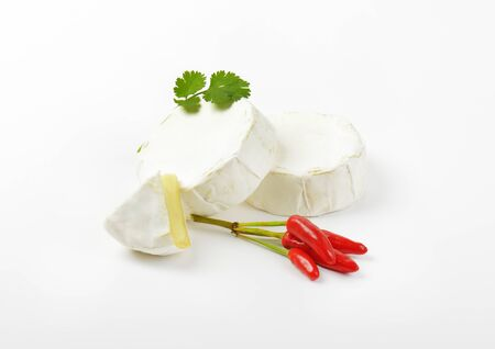 hermelin: Wheels of soft white cheese and red chili peppers Stock Photo