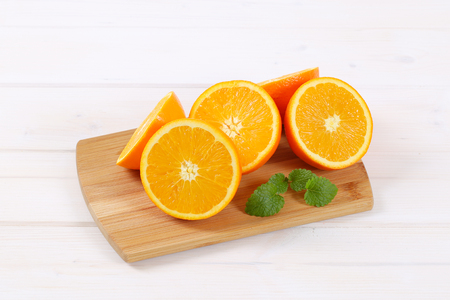group of halved oranges on wooden cutting board