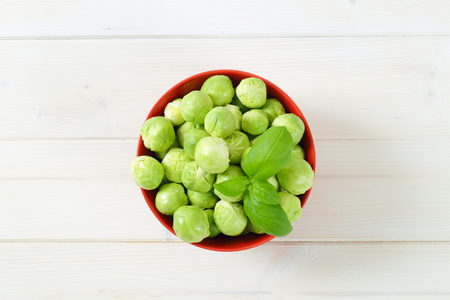 bowl of raw Brussels sprouts on white background
