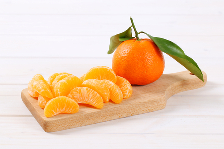 whole and peeled tangerines on wooden cutting board Stock Photo