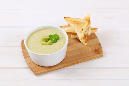 bowl of Brussels sprouts soup with toast on wooden cutting board