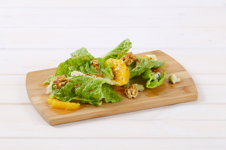 Chinese cabbage salad with orange, walnuts and blue cheese on wooden cutting board Stock Photo