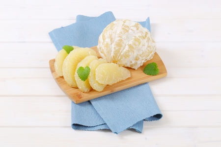 peeled and sliced pomelo on wooden cutting board Stock Photo