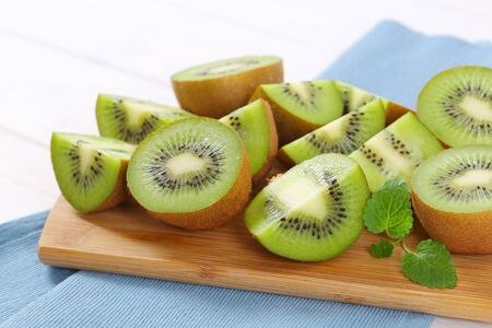 fresh kiwi fruits cut into halves and quarters on wooden cutting board