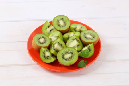 fresh kiwi fruits cut into halves and quarters on red plate Stock Photo