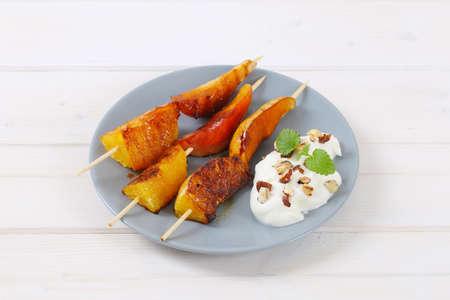 pinchos balsámicos de frutas glaseadas (pera y naranja) y yogur espolvoreado con avellanas picadas