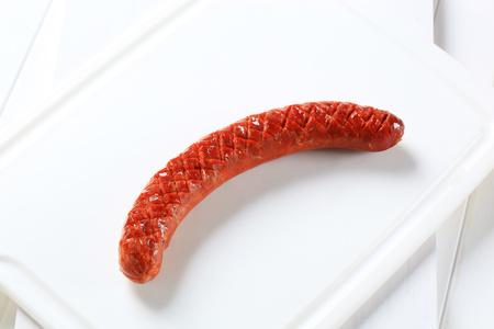 Saucisse épicée grillée sur planche à découper blanche