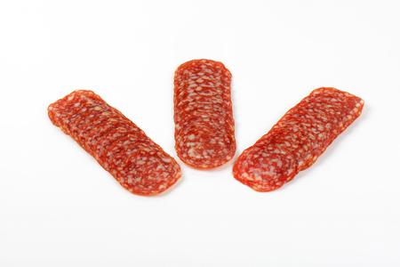 thin slices of salami arranged on white background Stock Photo