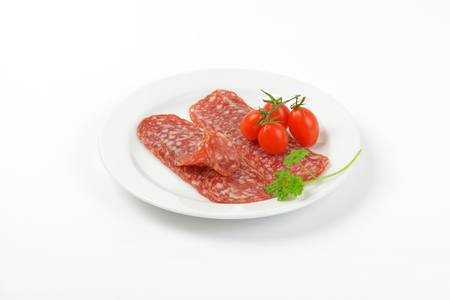 thin slices of salami and cherry tomatoes on white plate