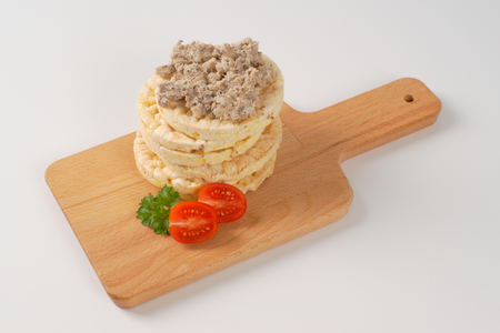 sardine: slices of puffed rice bread with fish spread on wooden cutting board