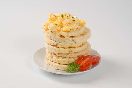 slices of puffed rice bread with scrambled eggs on white plate Stock Photo
