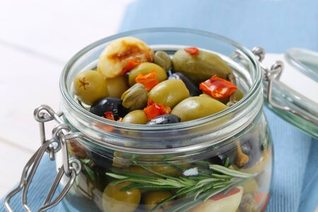 caper: jar of pickled olives, capers, caper berries and garlic