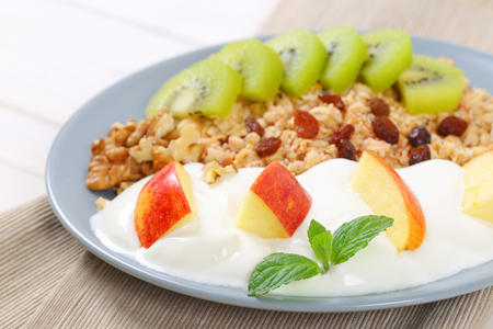 plate of muesli with yogurt and fresh fruit - close up Stock Photo