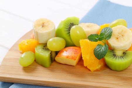 pila de ensalada de fruta fresca en la tabla de cortar de madera - de cerca