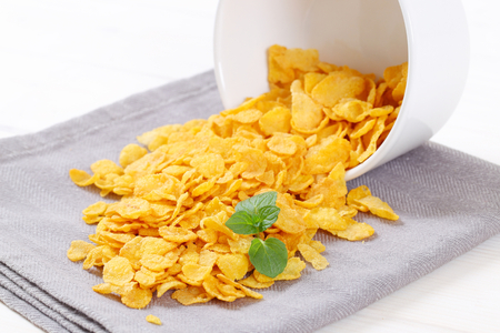 pile of corn flakes spilt out on grey place mat - close up Stock Photo