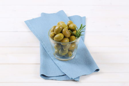glass of green olives with fresh rosemary on blue place mat