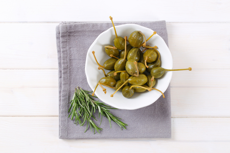 caper: bowl of pickled caper berries on grey place mat Stock Photo
