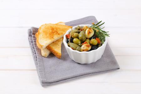 tazón de aceitunas en vinagre, alcaparras y bayas de alcaparras servidas con pan tostado Foto de archivo