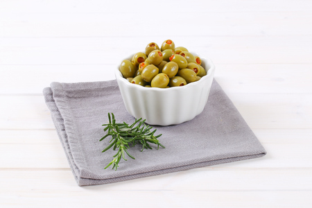 bowl of green olives stuffed with red pepper on grey place mat