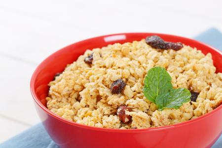 bowl of granola with hazelnuts and raisins - close up