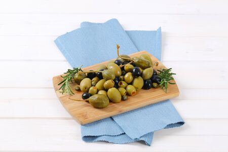 caper: pile of pickled olives, capers and caper berries on wooden cutting board