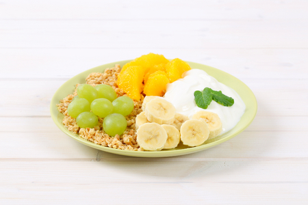 plate of muesli with white yogurt and fresh fruit on white background