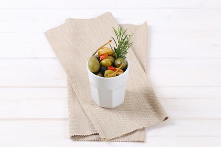 Tasse gebeizte Oliven, Kapern, Kapernbeeren und Knoblauch Standard-Bild - 77706730